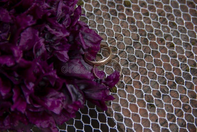 Les anneaux de mariage se trouvent sur une grille des briques rouges Les anneaux de mariage se trouvent à côté d'une fleur pourpr images libres de droits