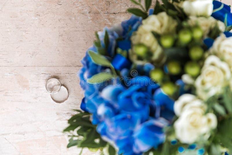 Les anneaux de mariage se trouvent sur une surface en bois à côté d'un groupe de fleurs image libre de droits