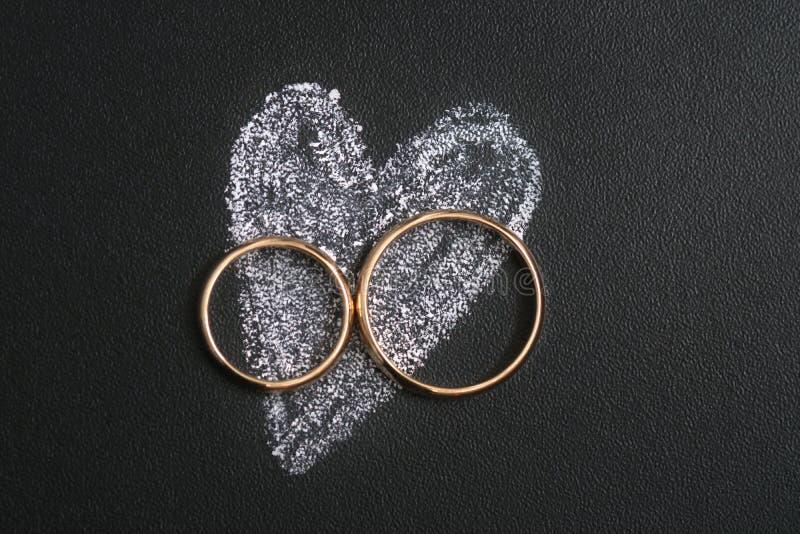 Les anneaux et le coeur de mariage dessinant avec calfatent sur le calkboard image stock