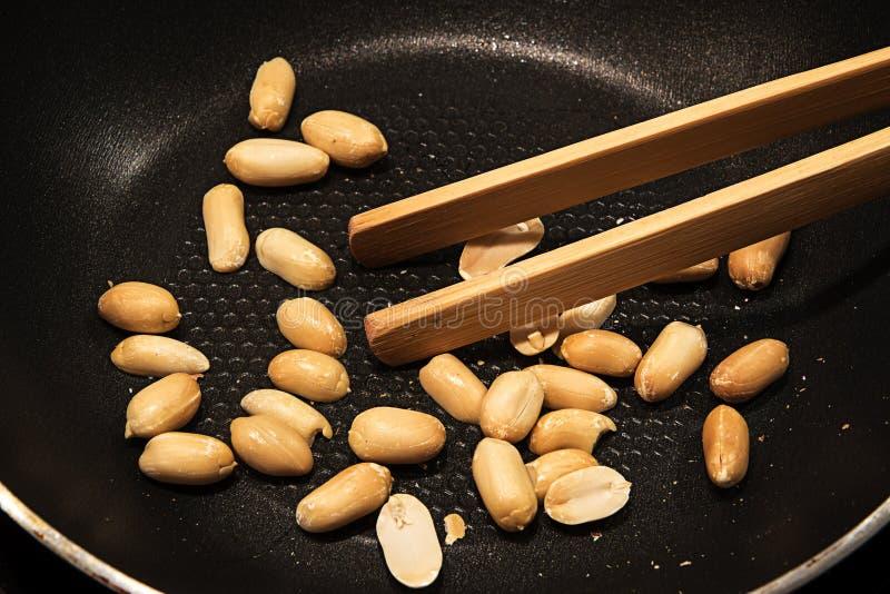 Les arachides épluchées ont rôti dans une casserole noire comme casse-croûte ou pour faire cuire Asia image libre de droits