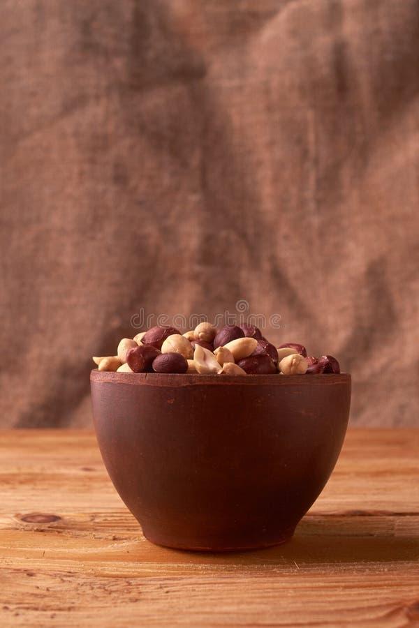 Les arachides cuites à la friteuse en argile roulent au-dessus du fond en osier rustique Foyer sélectif photo libre de droits