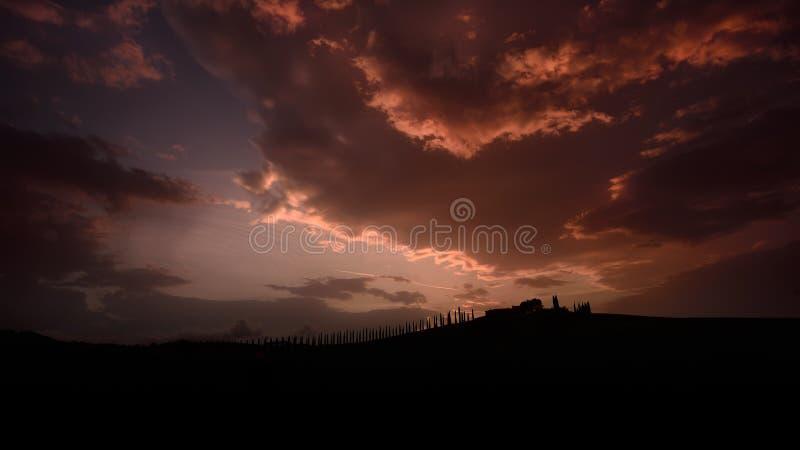 Les arbres de cyprès célèbres de la Toscane avec la maison d'agriculteur sur le coucher du soleil avec le rayon s'allument photos stock