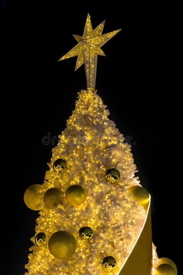 Les arbres de Noël décorés d'or avec des lumières se tiennent le premier rôle photo libre de droits