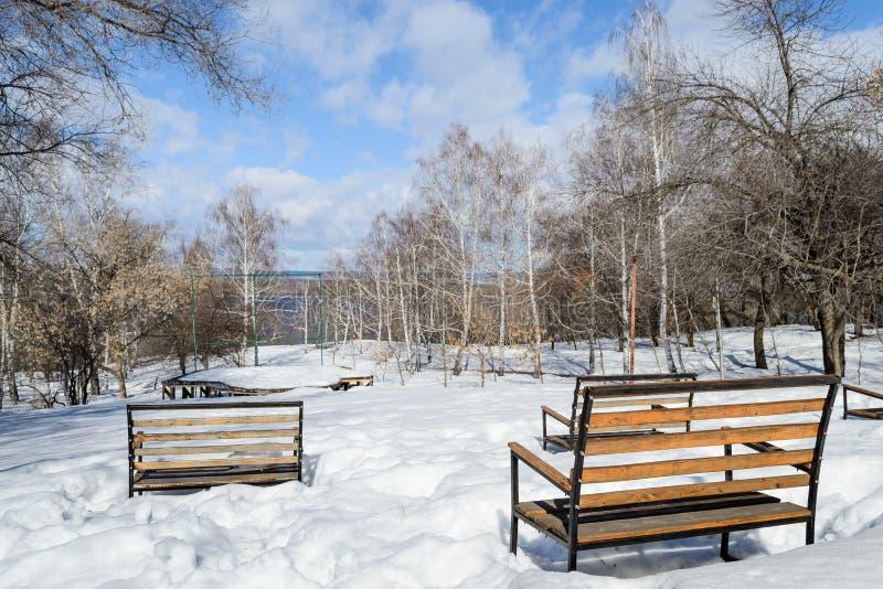 les arbres et les bancs couverts de neige dans la ville se garent Un bon nombre de neige images libres de droits