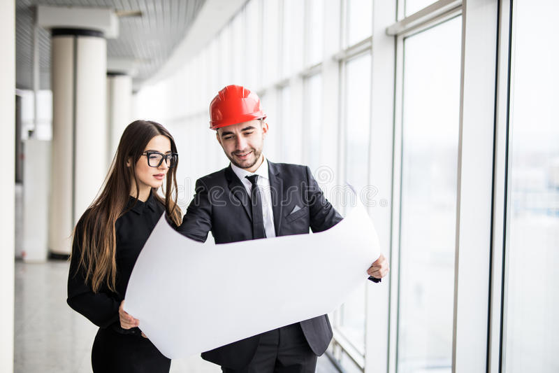 Les architectes d'homme d'affaires regardent l'architecte de papier de femme d'affaires de plan dans le bureau pour discuter des  photos libres de droits