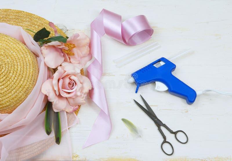 Les articles pour décorer un capot inclut un chapeau de paille, des ciseaux de cru, des roses en soie et une arme à feu de colle  images libres de droits