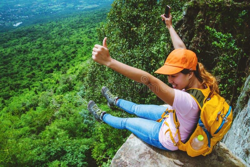 Les Asiatiques de femmes voyagent pour d?tendre pendant les vacances Reposez-vous sur la falaise Sur le Moutain images libres de droits