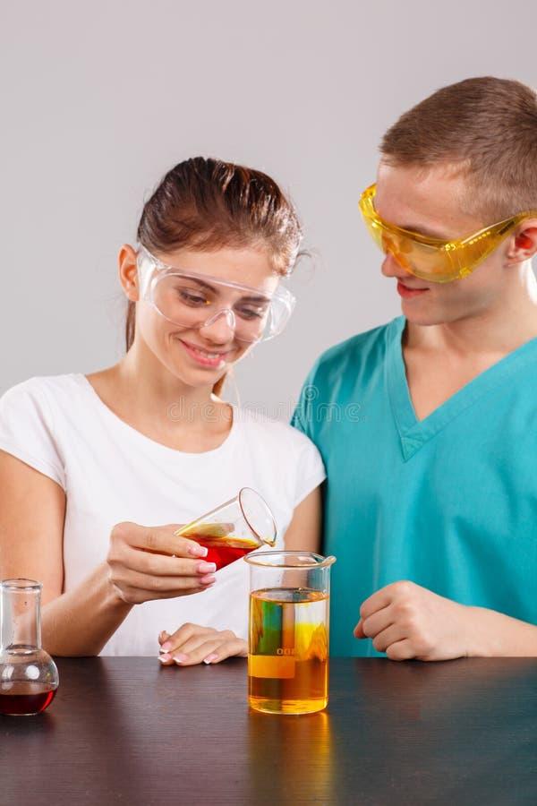 Les assistants d'une paire, la fille verse le liquide orange d'un petit verre de mesure dans un grand verre image stock