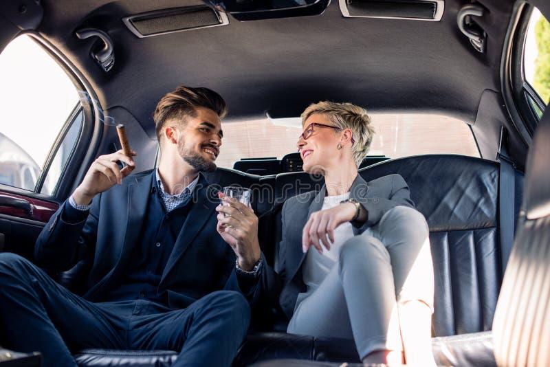 Les associés ont la boisson dans la limousine photo stock
