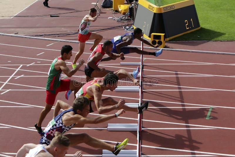 Les athlètes courant des obstacles de 110 mètres chauffe sur le championnat du monde U20 d'IAAF à Tampere, Finlande 11ème images stock