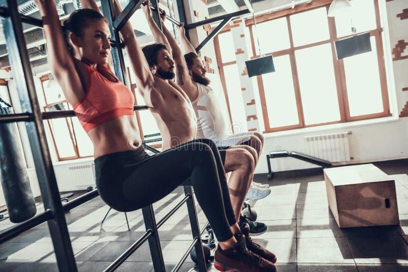 Les athlètes Hang On Horizontal Bar With ont noyé des jambes images stock