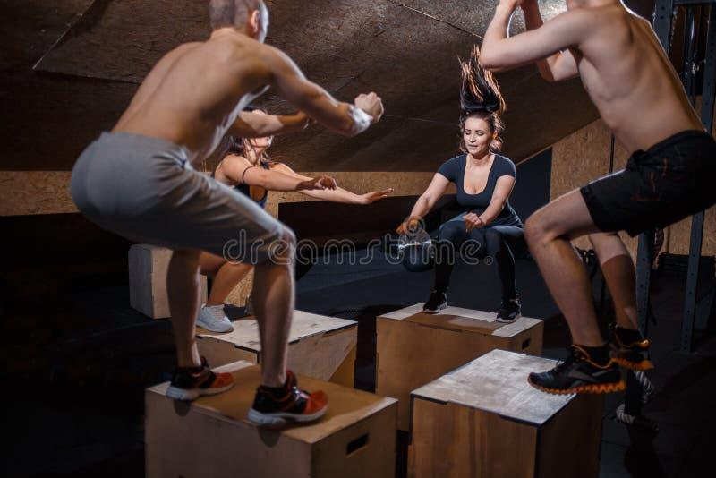 Les athlètes masculins et féminins faisant la boîte saute au gymnase photo libre de droits