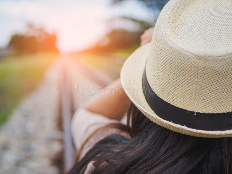 Les attentes noires et blanches de femme de voyageur s'exercent sur le chemin de fer photos stock