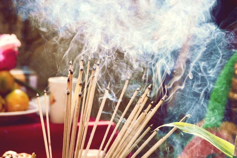 Les bâtons brûlants d'encens ont gravé en refief dans un pot d'encens Il y a beaucoup de fumée image libre de droits