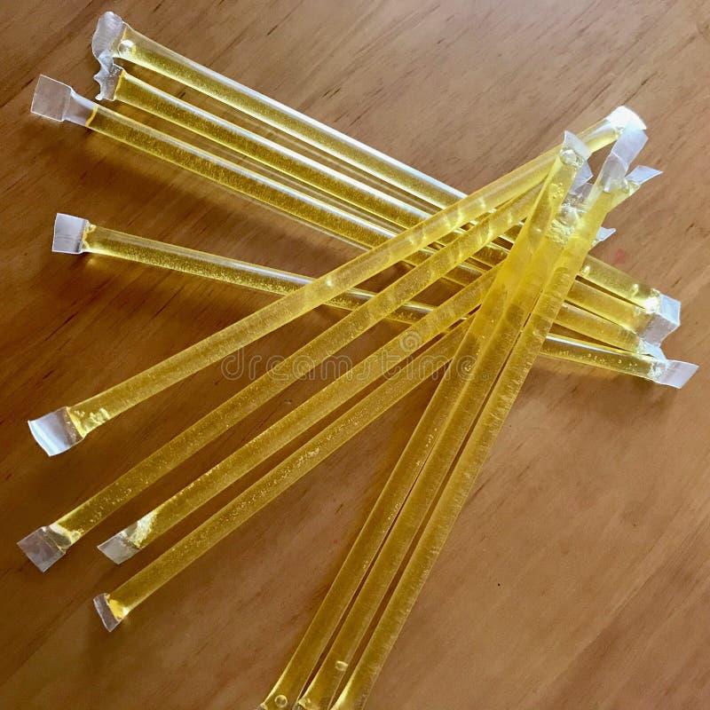 Les bâtons jaunes d'abeille se trouvent admirablement sur la table de cuisine en bois, dessert organique savoureux de miel image stock