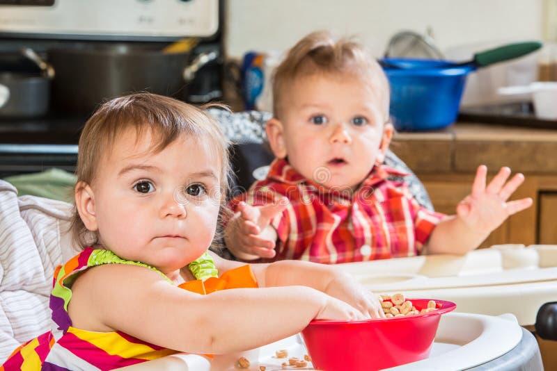 Les bébés mangent le petit déjeuner images libres de droits