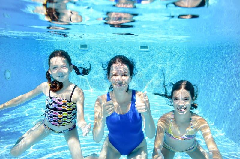 Les bains de famille dans la piscine sous l'eau, la mère active heureuse et les enfants ont l'eau du fond d'amusement, la forme p photo stock