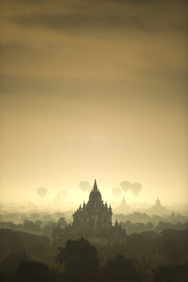 Les ballons à air chauds de scène de lever de soleil volent au-dessus du champ de ville antique de pagoda en Bagan Myanmar Qualit images stock
