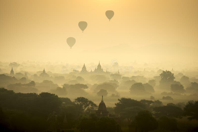 Les ballons à air chauds de scène de lever de soleil volent au-dessus du champ de ville antique de pagoda en Bagan Myanmar Qualit photos libres de droits