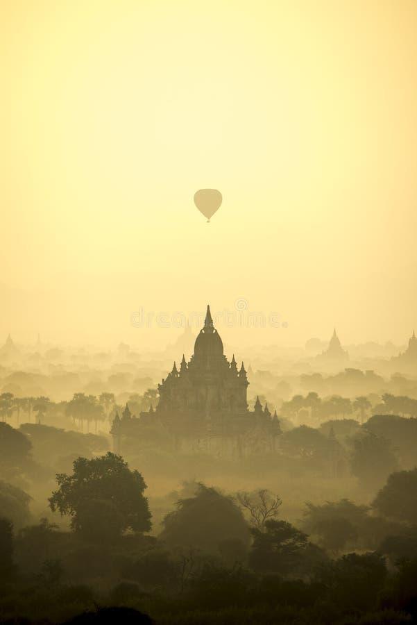 Les ballons à air chauds de scène de lever de soleil volent au-dessus du champ de ville antique de pagoda en Bagan Myanmar Qualit photographie stock
