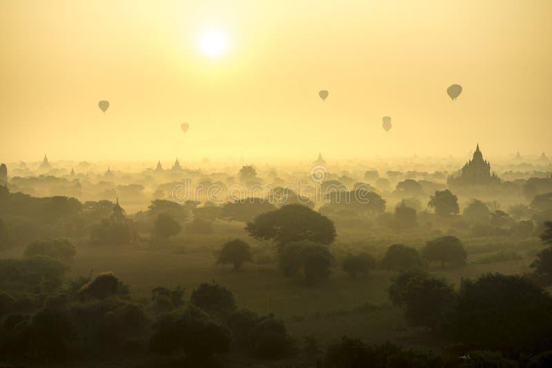 Les ballons à air chauds de scène de lever de soleil volent au-dessus du champ de ville antique de pagoda en Bagan Myanmar Qualit photo stock
