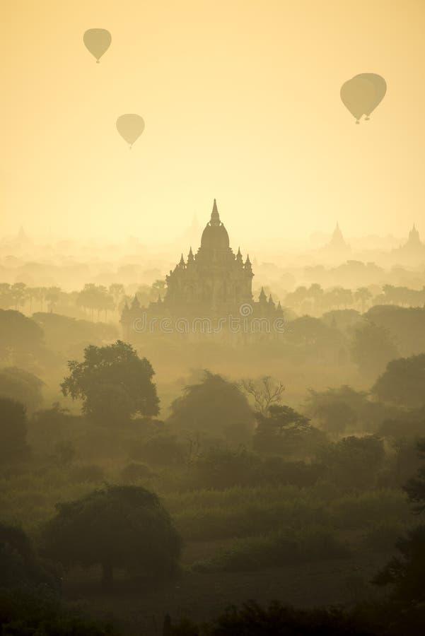 Les ballons à air chauds de scène de lever de soleil volent au-dessus du champ de ville antique de pagoda en Bagan Myanmar Qualit photographie stock libre de droits