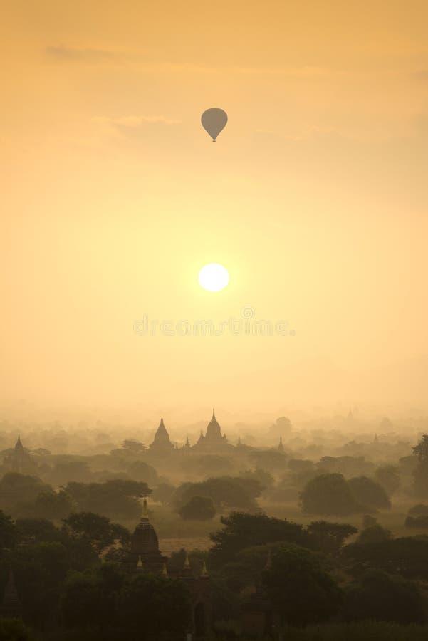 Les ballons à air chauds de scène de lever de soleil volent au-dessus du champ de ville antique de pagoda en Bagan Myanmar Qualit photos stock