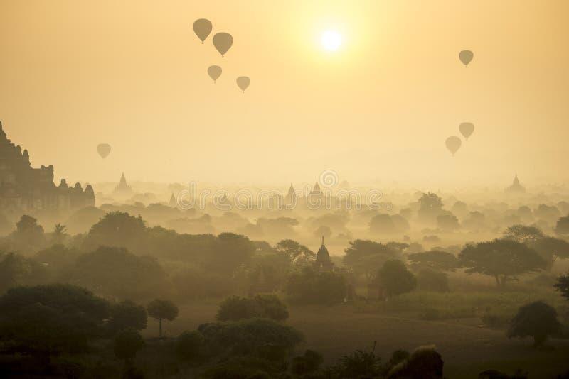 Les ballons à air chauds de scène de lever de soleil volent au-dessus du champ de ville antique de pagoda en Bagan Myanmar Qualit image libre de droits