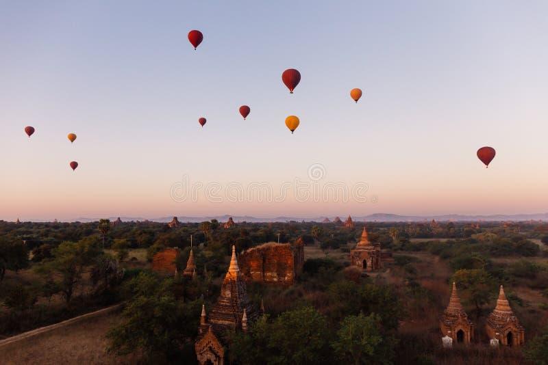 Les ballons à air chauds flottant autour du site birman d'héritage de pagoda pendant le lever de soleil aménagent en parc images libres de droits
