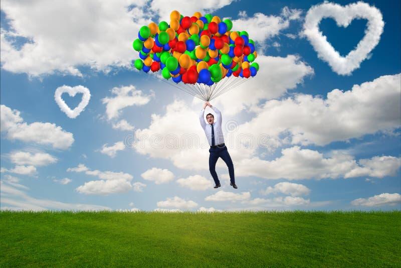 Les ballons de vol d'homme dans le concept romantique photo stock