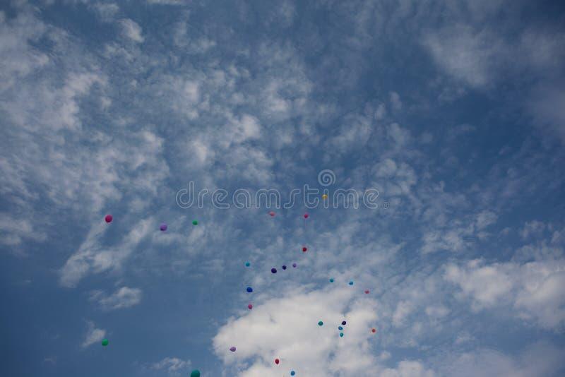 Les ballons gonflables volent dans le ciel nuageux image stock