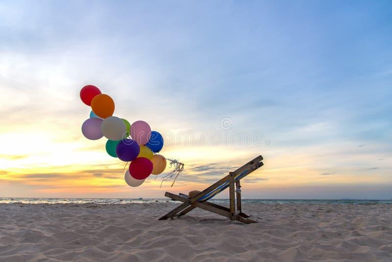 Les ballons multicolores avec la toile enfoncent pour détendent le jour ensoleillé de plage tropicale de coucher du soleil images stock