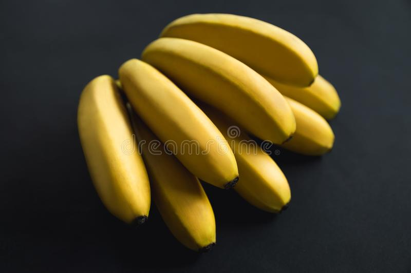 Les bananes m?res lumineuses jaunes se trouvent sur un fond noir Branche d?licieuse de banane fruit sur un fond noir images stock