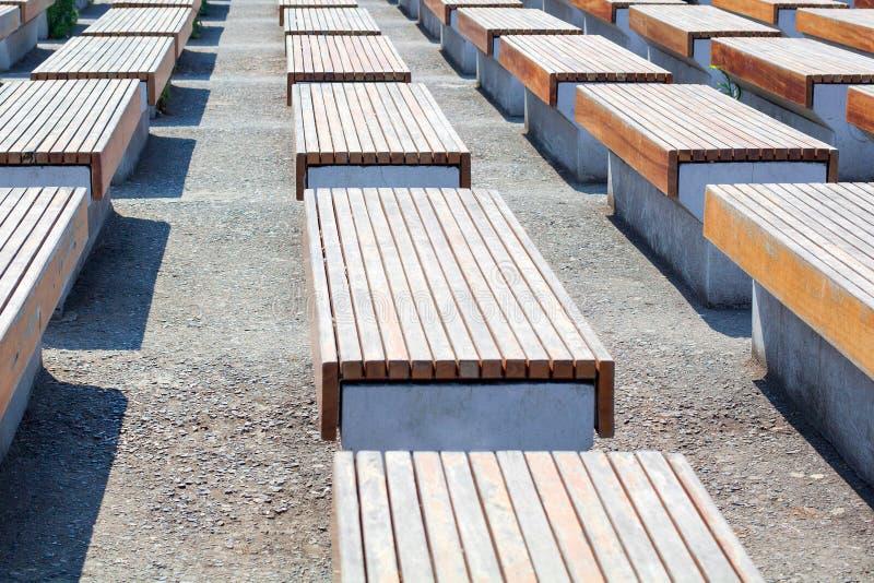 Les bancs vides en bois et le support de surface en béton dans plusieurs rangées sur la rue en parc sur l'asphalte, personne est  image stock