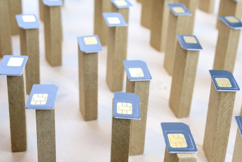 Les barres en bois se tenant chaotiquement sur eux sont les cartes mises de SIM, téléphone mobile abstrait photos stock