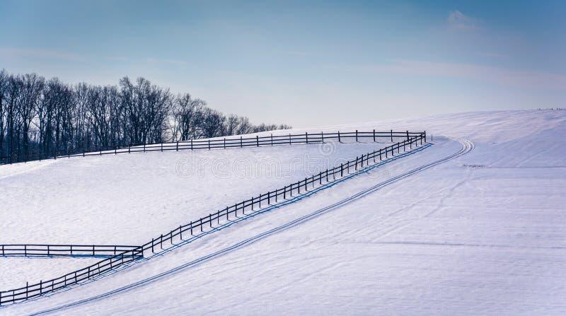 Les barrières sur une neige ont couvert le champ de ferme dans Carroll County rurale, mars photo libre de droits