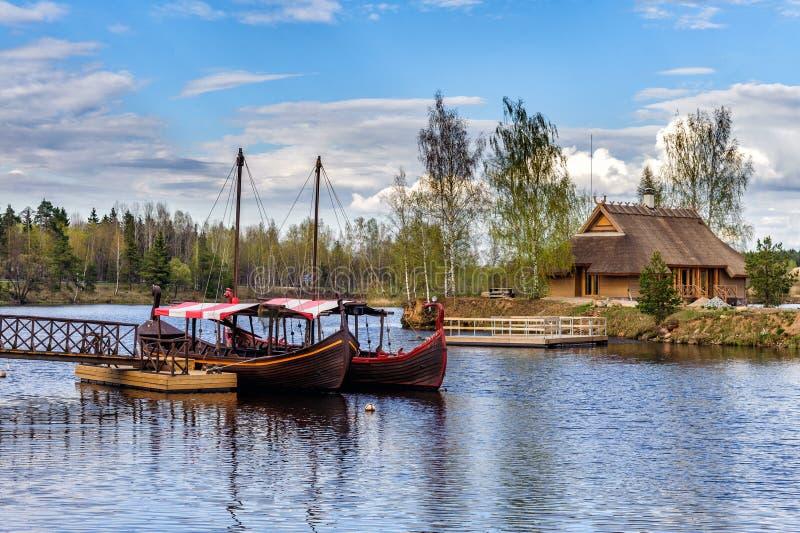 Les bateaux à voile en bois lettons s'approchent du petit pilier à la ville de Liepkalni, Lettonie photos libres de droits