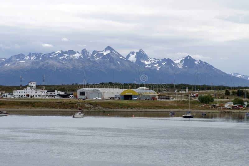 Les bateaux dans Ushuaia hébergent avec l'aéroport à l'arrière-plan images libres de droits