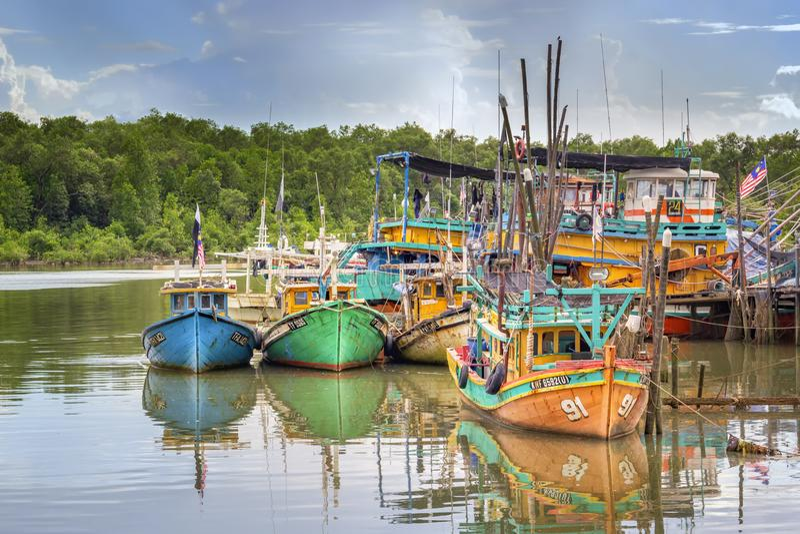 Les bateaux de pêche colorés se tiennent dans une crique sur la rivière en Asie du Sud-Est contre le ciel bleu images libres de droits