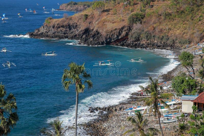 Les bateaux de pêche traditionnels vont à la sécurité de la baie dans Bali Une île de roche outre de la côte avec la végétation t photographie stock