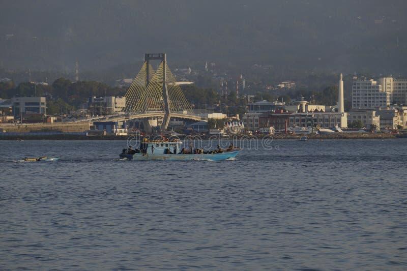 Les bateaux de pêche vont à la mer dans l'environnement urbain de Manado image libre de droits