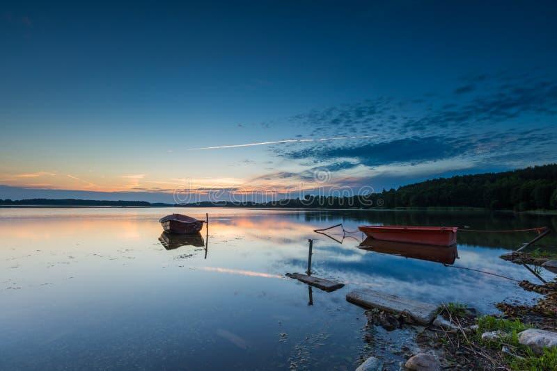 Les bateaux de pêcheur amarrés sur le lac étayent sous le ciel de coucher du soleil images stock