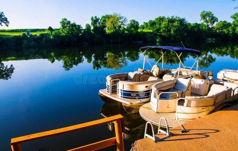 Les bateaux de ponton de réflexions du lac LBJ sur l'eau ont accouplé prêt pour l'eau libre images stock