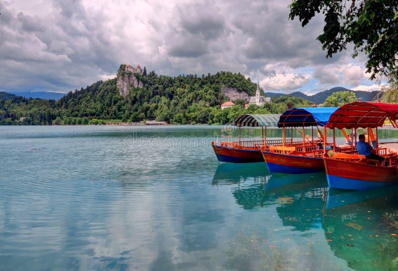 Les bateaux de touristes dans le premier plan, île saignée est dans le backgroun photographie stock
