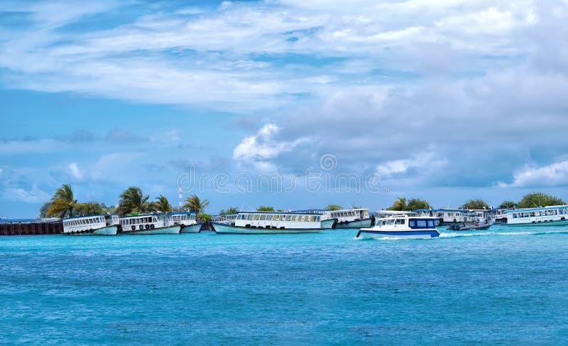 Les bateaux ont amarré au port masculin, île Maldive sur un clou bleu ensoleillé images stock