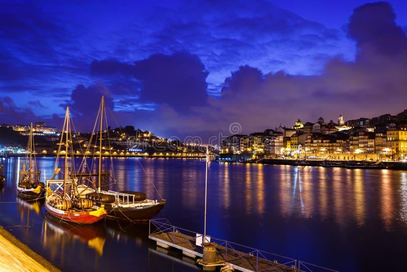 Les bateaux ont amarré le long de la façade d'une rivière avec des lumières se reflétant en rivière de Douro à Porto, Portugal photographie stock libre de droits