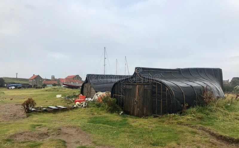 Les bateaux renversés donnent un nouveau sens à la notion de 'hangars à bateaux' photo stock