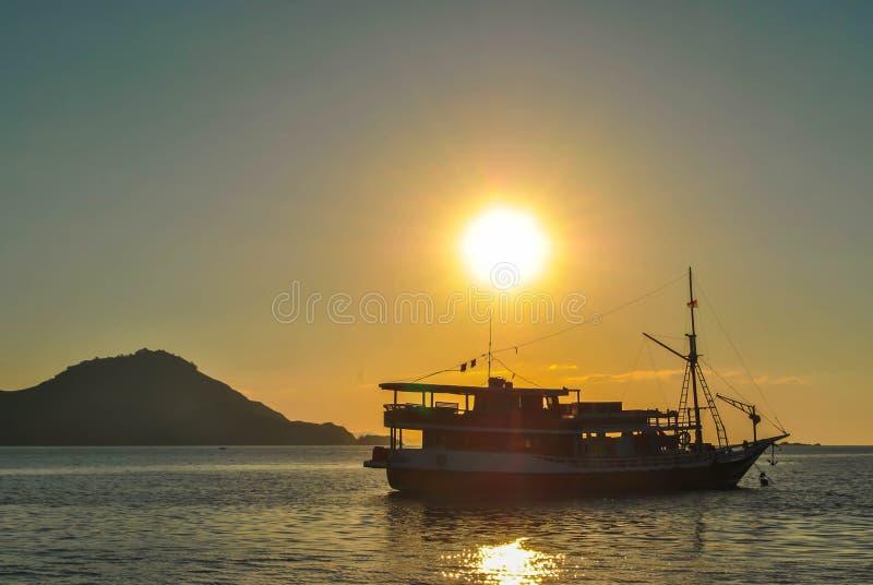 Les bateaux silhouettent en mer sur le coucher du soleil Beau coucher du soleil en île tropicale de Komodo, Labuan Bajo, avants,  photo libre de droits
