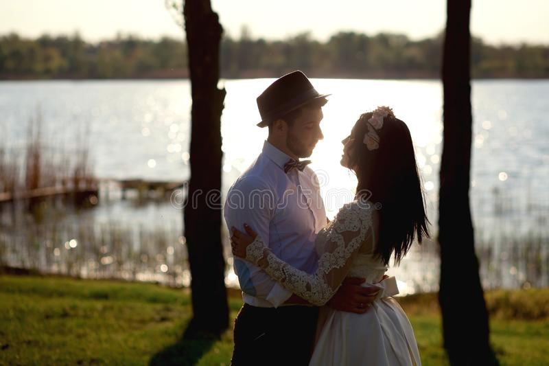 Les beaux, élégants couples étreignant près de la rivière au coucher du soleil, les jeunes mariés s'admirent, regardent dans les  photos stock
