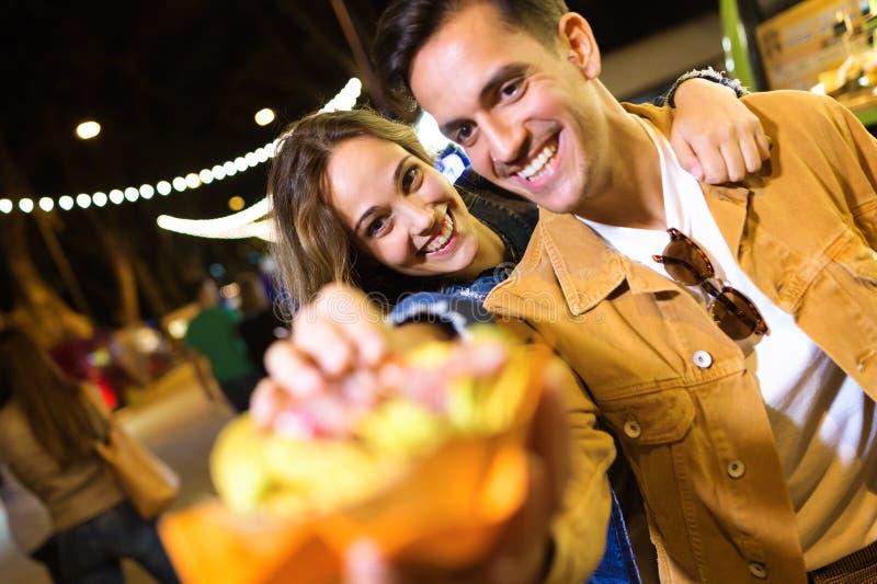 Les beaux couples attrayants mangeant des pommes de terre mangent ensemble dedans le marché de la rue photos stock